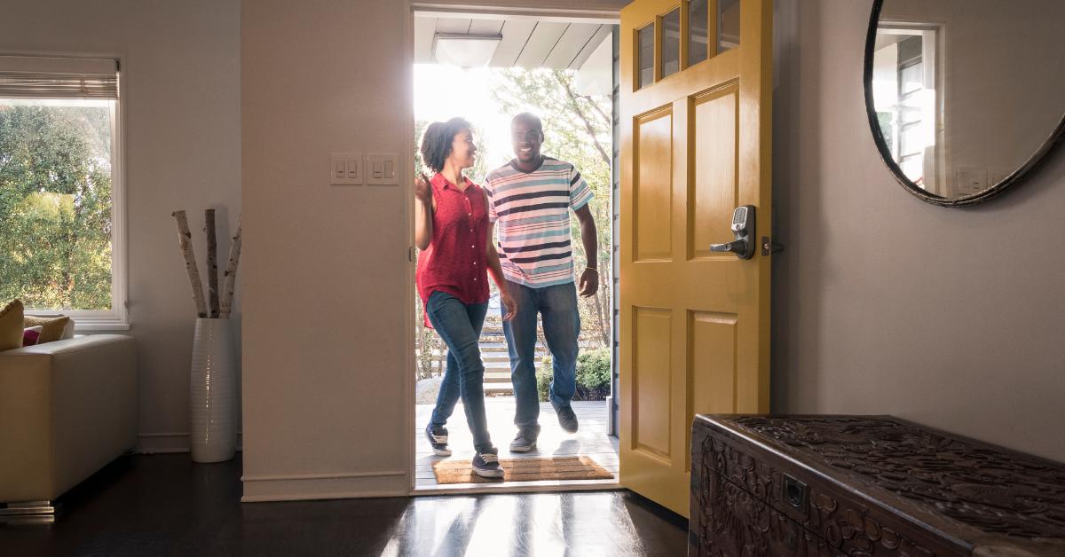 Couple walking in the front door of their home
