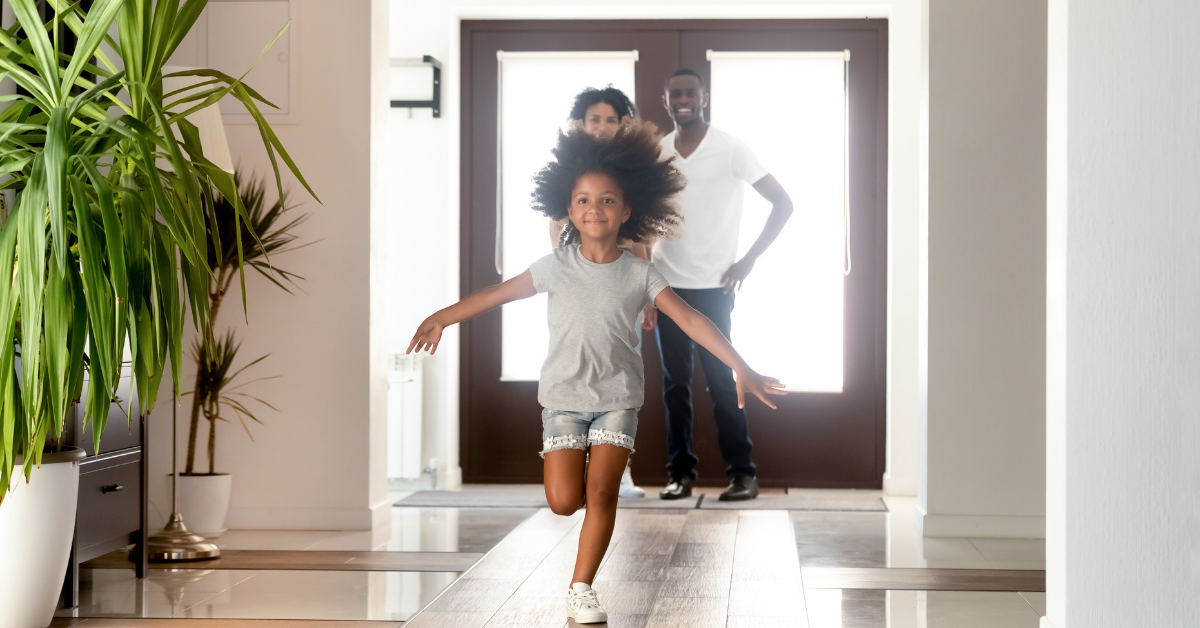 Young girl running into a new home with parents standing by